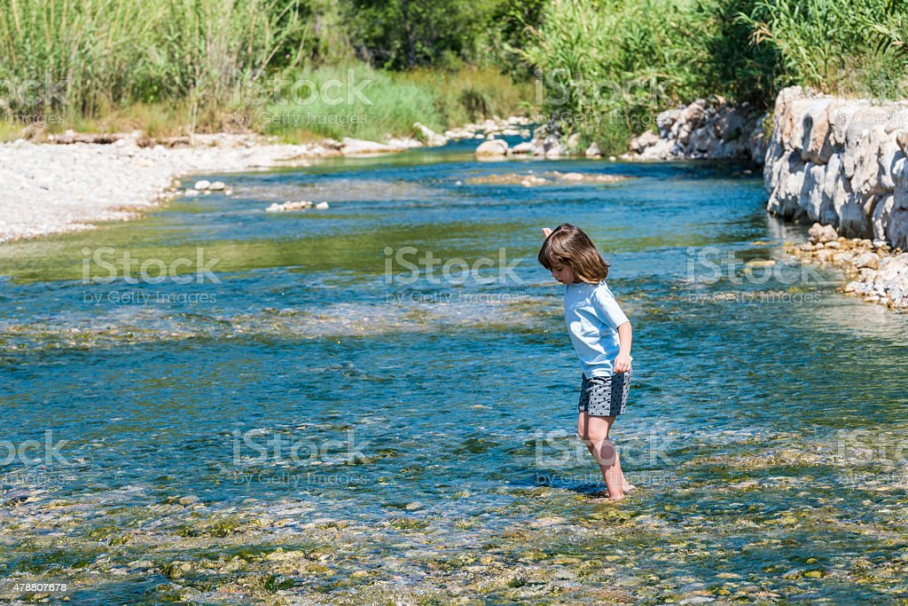 Little girl crossing a river stock photo