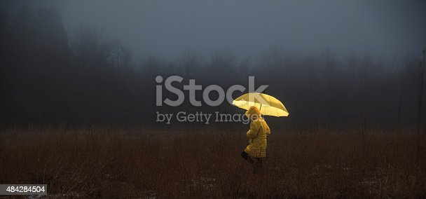 Little girl in the yellow coat with umbrella crossing the field in fog. Homage to the Little Red Riding Hood