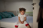 Focus on a little girl crying in bedroom. Father is punishing her.