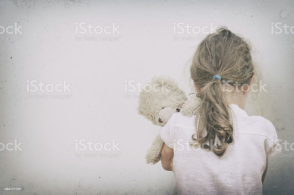 Little girl crying in the corner. stock photo