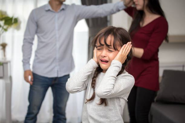 Little girl crying while parents quarrel. Closing the ears, 5-10 years old, family violence concept. stock photo