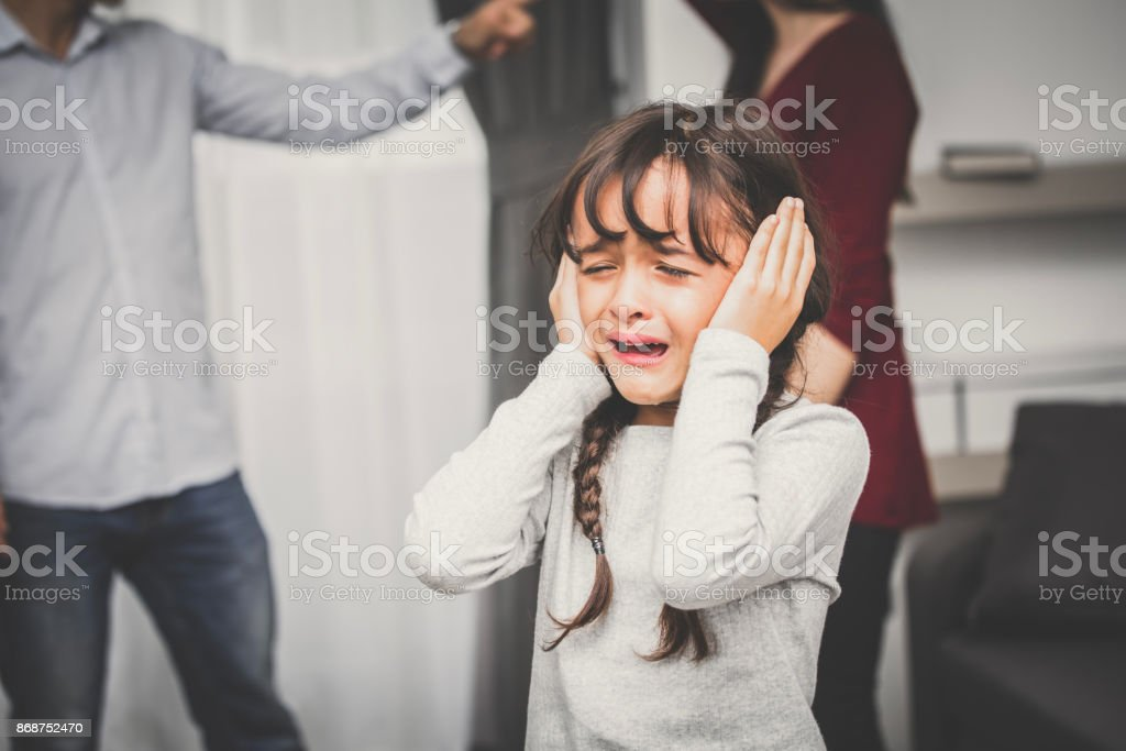 Little girl crying while parents quarrel. Closing the ears, 5-10 years old, vintage tone. stock photo