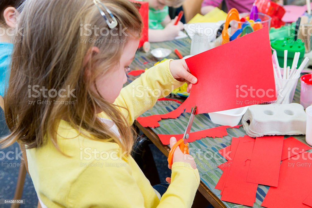 Little Girl Cutting Paper stock photo