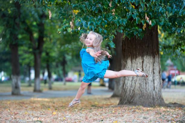 Little girl dancer jump in summer park stock photo