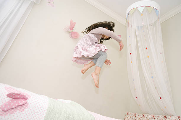 kleines mädchen tanzen und springen auf ihrem bett - mädchenraum vorhänge stock-fotos und bilder