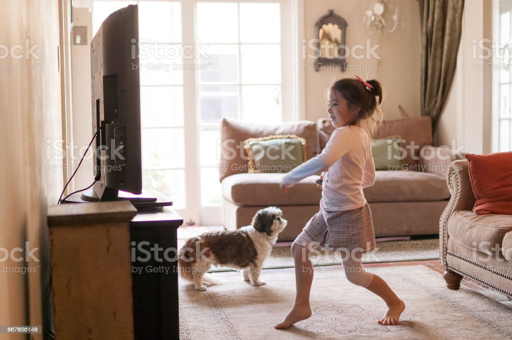 Little girl dancing in front of the TV at home - Royalty-free 6-7 Years Stock Photo