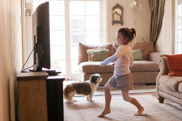 Little girl dancing in front of the TV at home stock photo