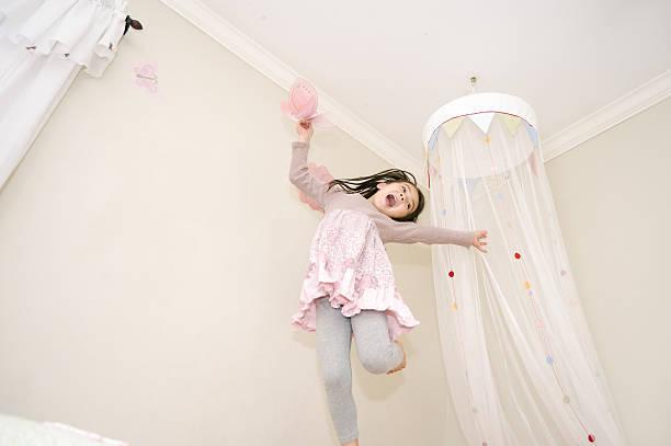 kleines mädchen tanzen auf ihrem bett mit einem schmetterling - mädchenraum vorhänge stock-fotos und bilder