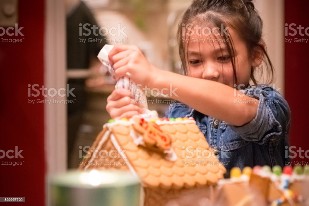 Little girl decorating Christmas gingerbread house royalty-free stock photo