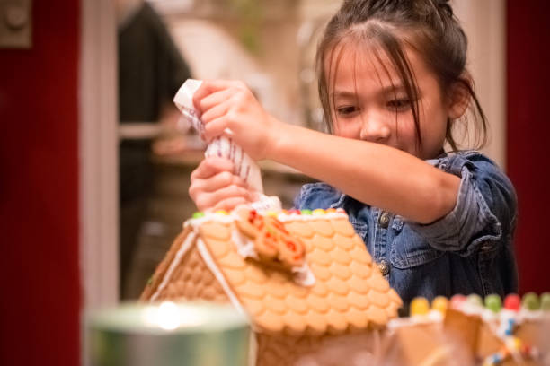 Little girl decorating Christmas gingerbread house stock photo