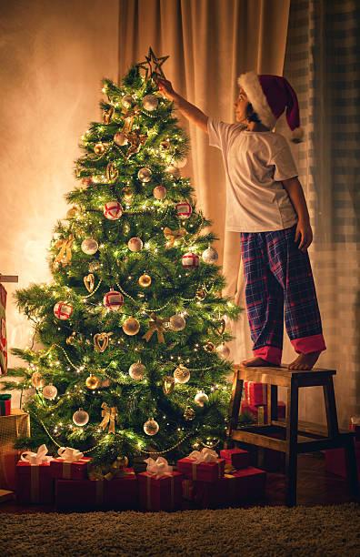 bambina decorare l'albero di natale - santa claus tiptoeing foto e immagini stock