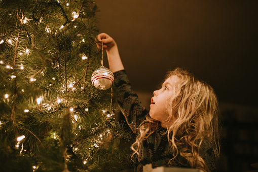 A child reaches up high to hang an ornament on the lighted Christmas tree in her home.