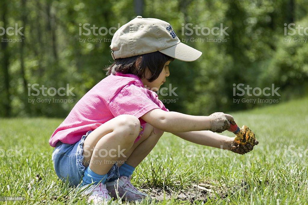 Little Girl Digging in the Dirt stock photo