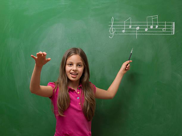 menina direção coro de música antes de quadro-negro - desenhos de notas musicais - fotografias e filmes do acervo