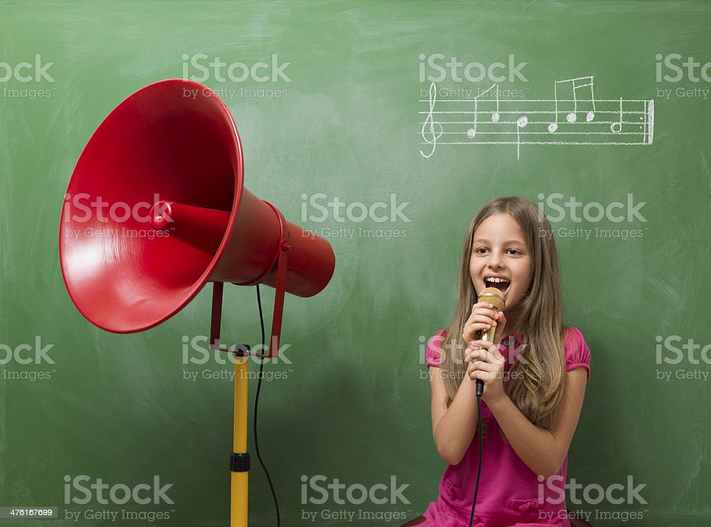 Little girl directing chorus for music before blackboard royalty-free stock photo