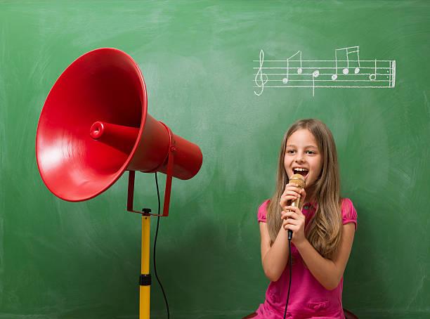 kleines mädchen regeln chorus für musik vor der tafel - lautbildungsspiele stock-fotos und bilder