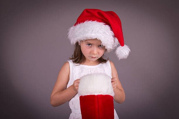 Little girl disappointed with her Christmas stocking stock photo