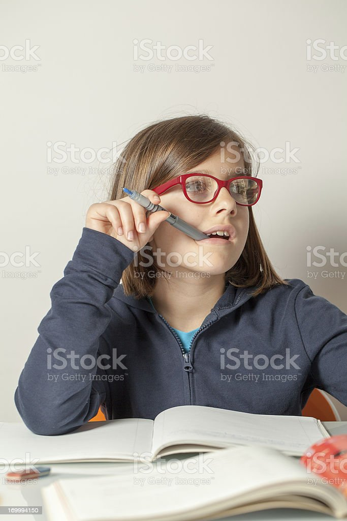 Little Girl Distracted While Doing Her Homework stock photo