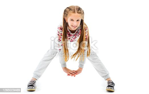 Little girl do forward bend exercise in grey sportwear, isolated on white background. Healthy lifestyle