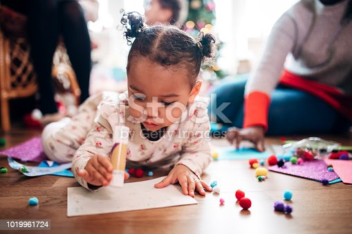 A little girl does art and craft on Christmas Day; her mother can be seen in the background.