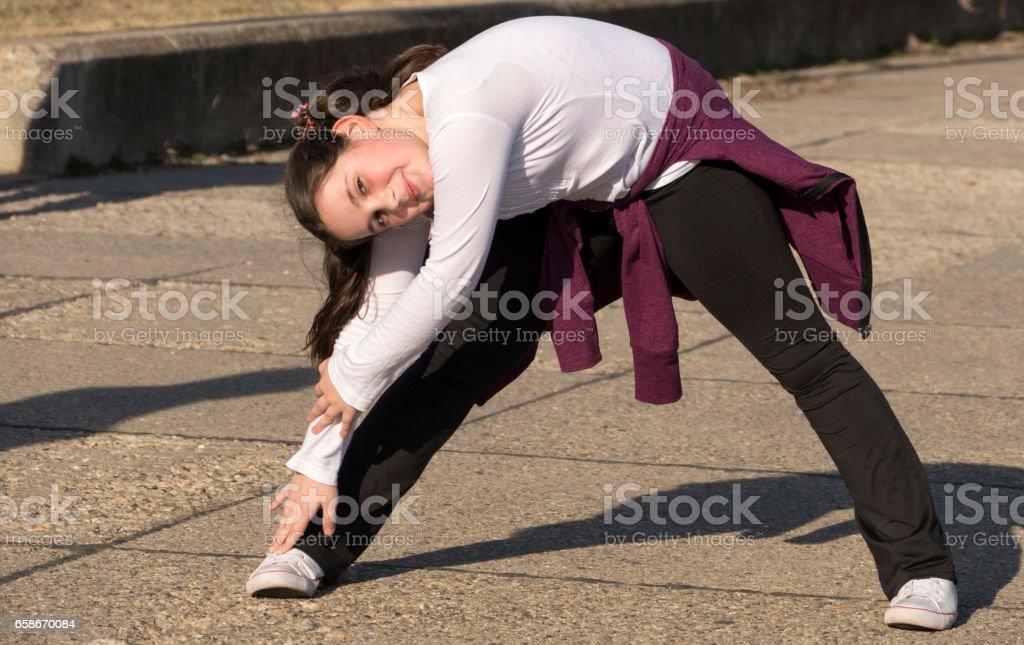 Little girl doing exercises in park stock photo