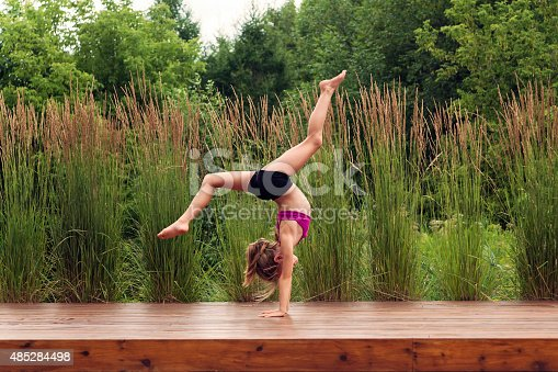 Your kid is full of energy? Maybe she's a future gymnast, like this young lady, who spent most of her days perfecting her moves. She is standing on her hands on a wooden floor outdoors in summer nature. Full length horizontal shot with copy space.