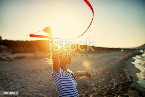 istock Little girl doing gymnastics on the beach. 636343438