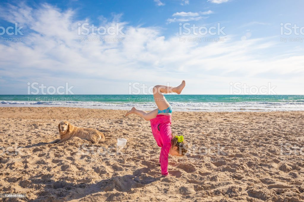little girl doing handstand on sand beach next to a dog stock photo