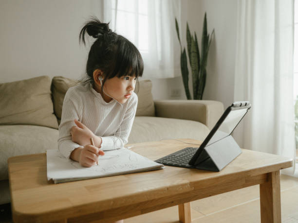 Little girl doing her homework with digital tablet. Young woman wearing headphones learning using digital tablet and teleconferencing apps in living room at home digital native stock pictures, royalty-free photos & images