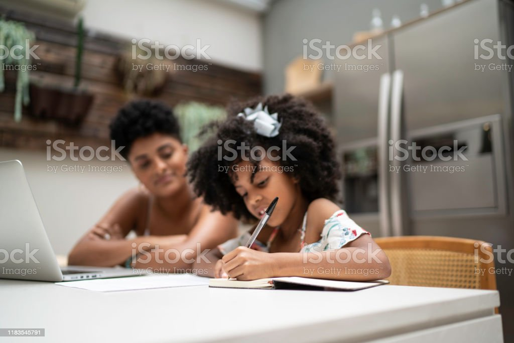 Little girl doing homework with her sister Little girl doing homework with her sister 20-24 Years Stock Photo