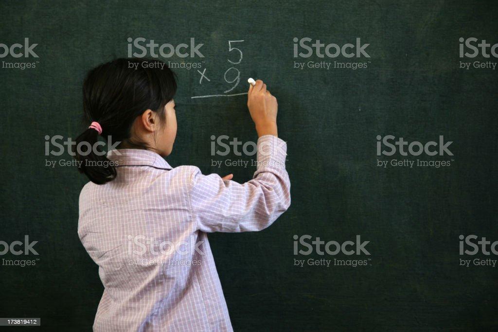 Little Girl Doing Math on Blackboard royalty-free stock photo