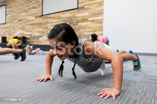 Adorable little girl demonstrates her strength while doing a pushup during gym class.
