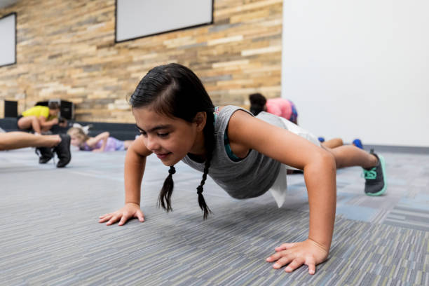 Little girl doing pushups in gym class stock photo