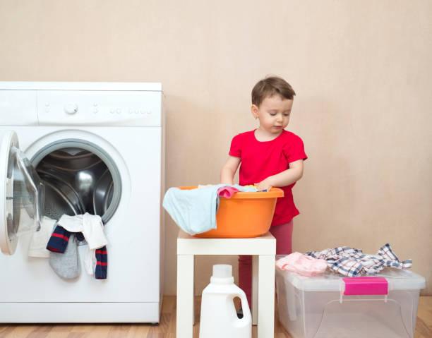 liten flicka gör tvätten nära en tvättmaskin - working from home bildbanksfoton och bilder