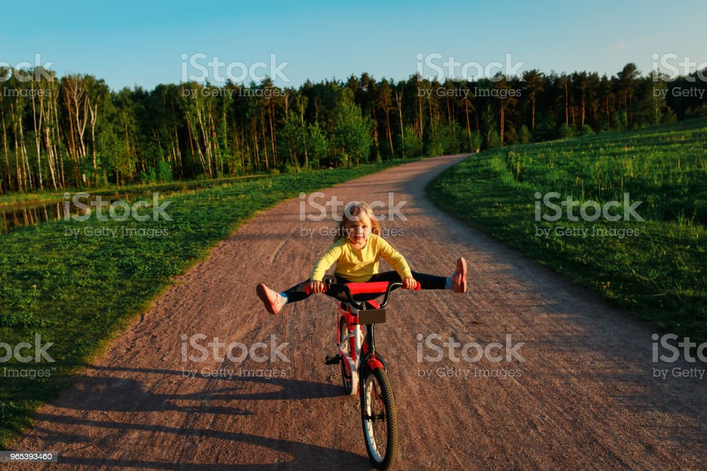 little girl doing tricks riding bike zbiór zdjęć royalty-free