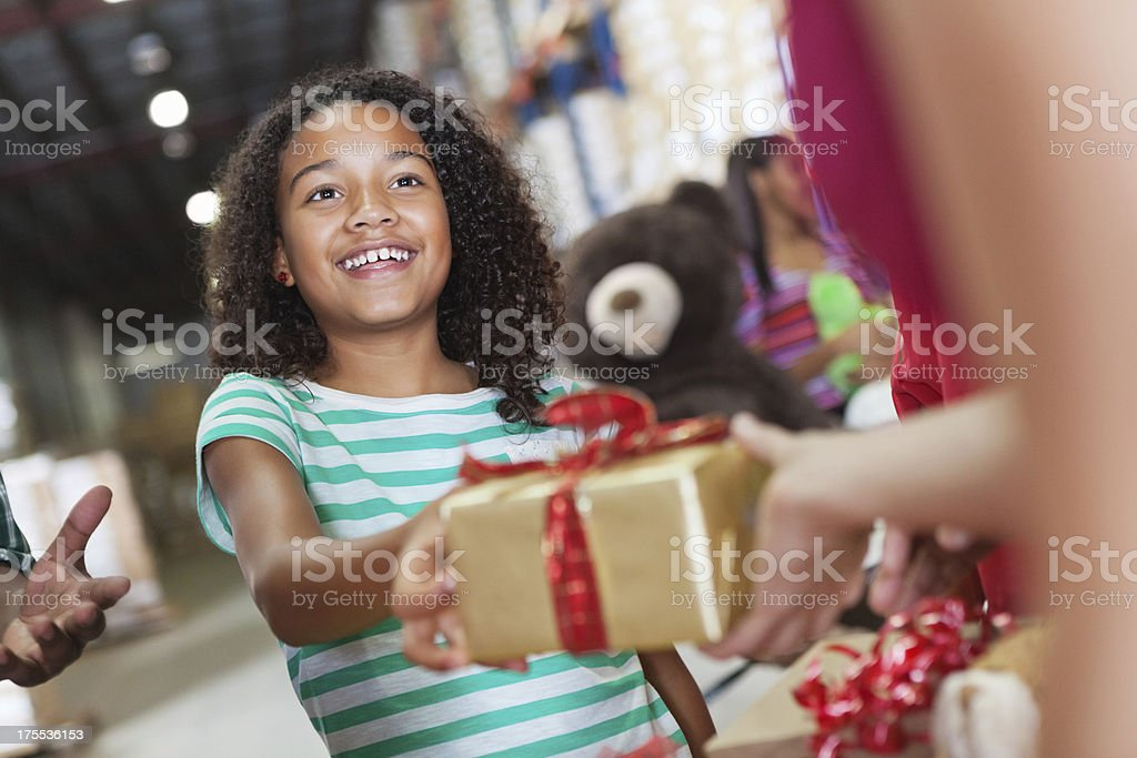 Little girl donating Christmas gift at toy donation charity drive stock photo