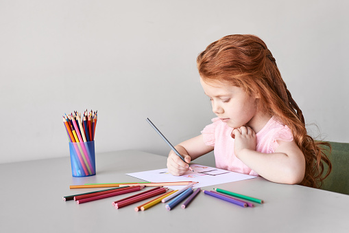Little girl drawing. Closed Locking Exercise. Homemade routine. School lessons. Write pencil on piece of paper. Kindergarten study. Elementary preschool. Woman kid student. Copyspace