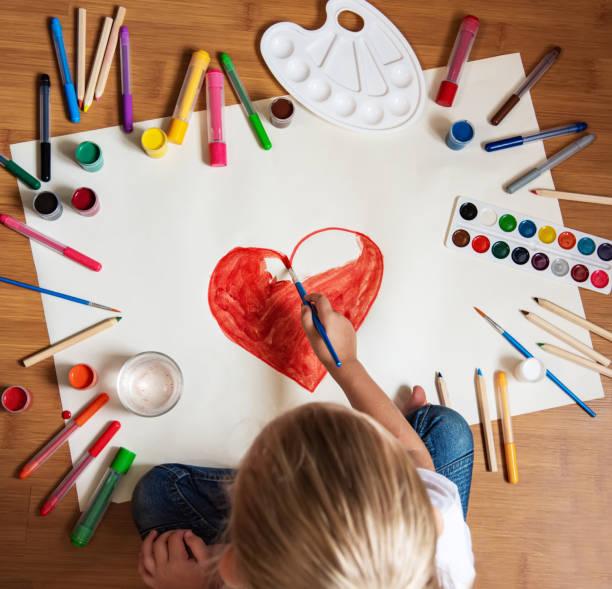 pequeña niña dibujando en papel - dibujar fotografías e imágenes de stock