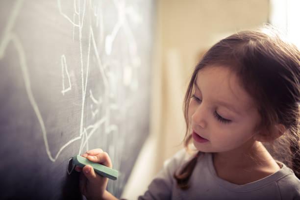 Kleines Mädchen auf Tafel zeichnen – Foto