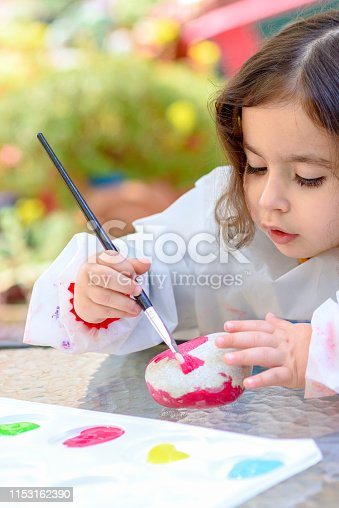 istock Little Girl Drawing On Stone Outdoors In Summer Sunny Day. 1153162390