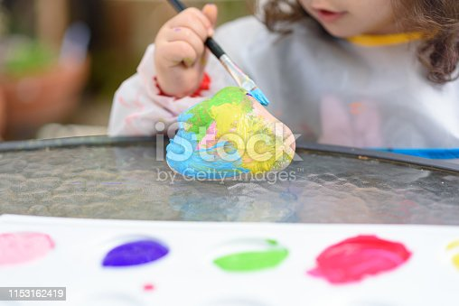 istock Little Girl Drawing On Stone Outdoors In Summer Sunny Day. 1153162419
