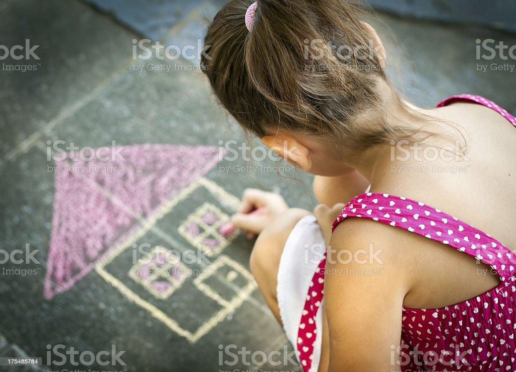 Little Girl Drawing on the sidewalk stock photo