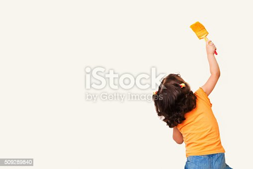 istock Little girl drawing something on wall background 509289840