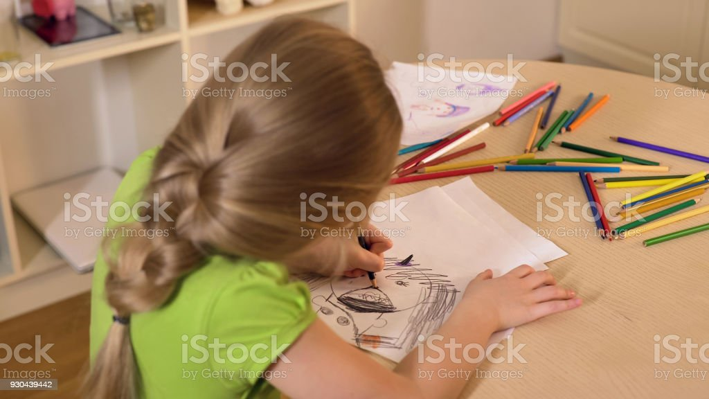 Little girl drawing stranger from her nightmare with black pencil, child fears stock photo