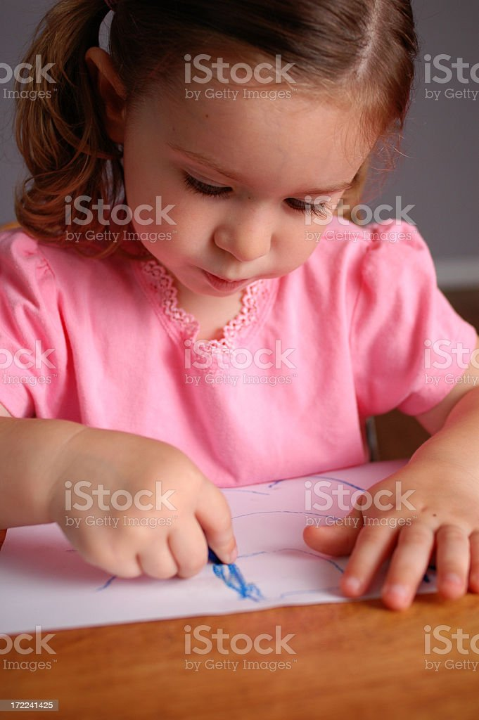 Little Girl Drawing while Sitting in School Desk royalty-free stock photo