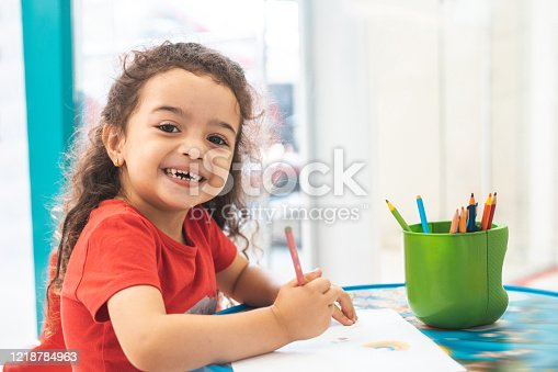 Little girl drawing with colorful pencils in daycare