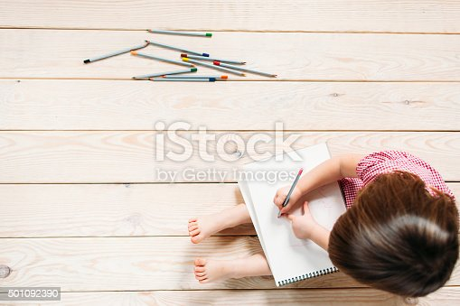 istock little girl drawing with colorful pencils 501092390