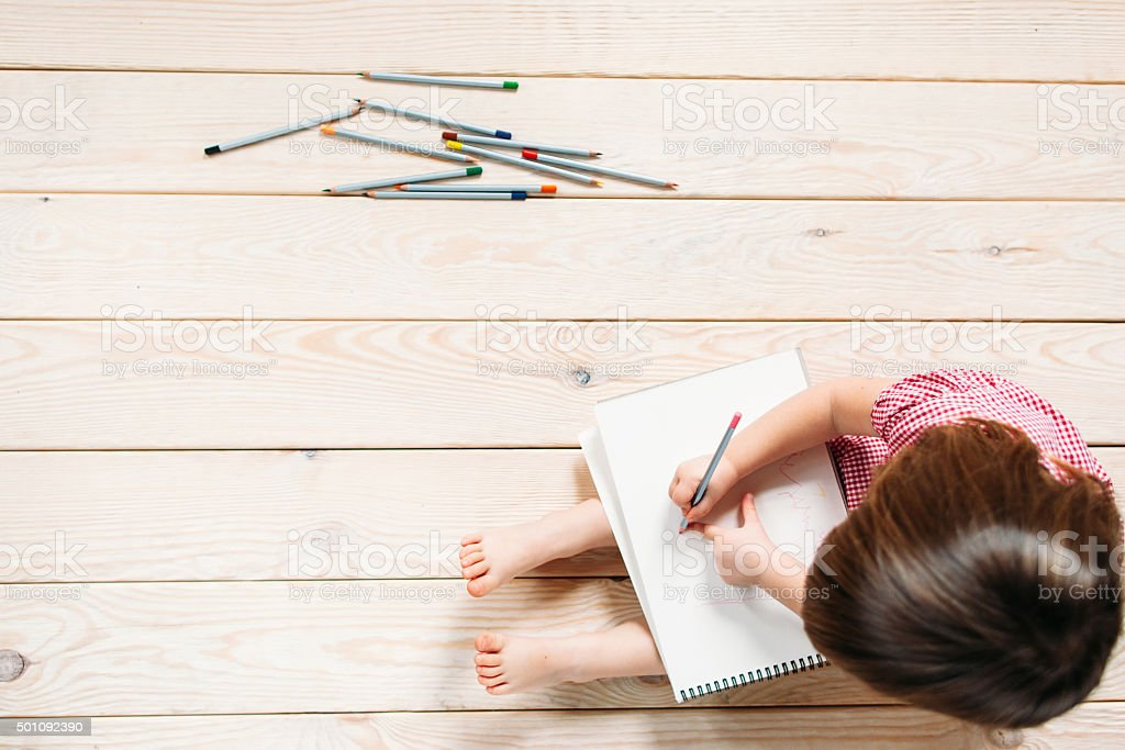 little girl drawing with colorful pencils stock photo