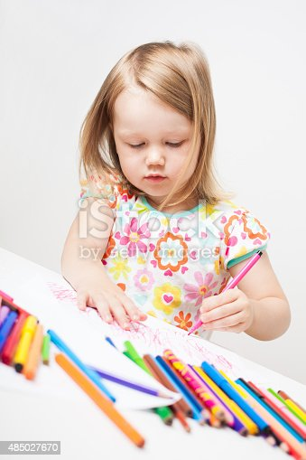 istock Little girl drawing with colourful pencils. 485027670