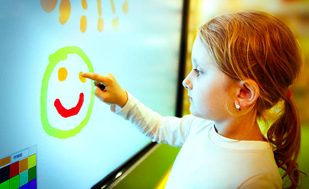 little girl drawing with finger on the touch screen - interactivity stock photos and pictures